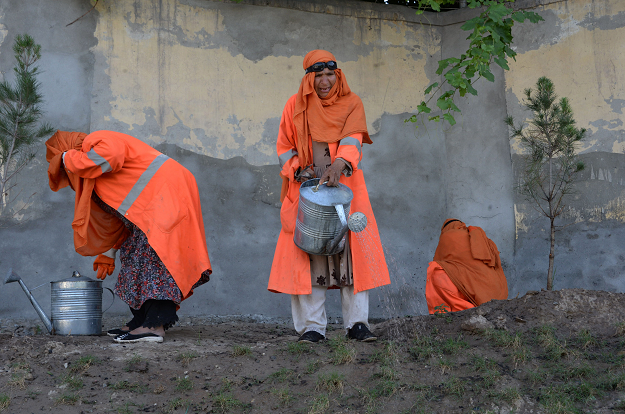 In this photograph taken on April 23, 2018, female Afghan municipality employees, supported by United Nations agency UN-Habitat, water a garden in Jalalabad. It may look like they're just planting and weeding, but for the women tending the public gardens of Jalalabad, the tasks represent far more: the rare chance to work outside the home in one of Afghanistan's most conservative and unstable provinces  PHOTO: AFP