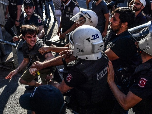 Turkish riot policemen beats a LGBT rights activist after Turkish authorities banned the event for a fourth year in a row, on July 1, 2018 in Istanbul. PHOTO: AFP