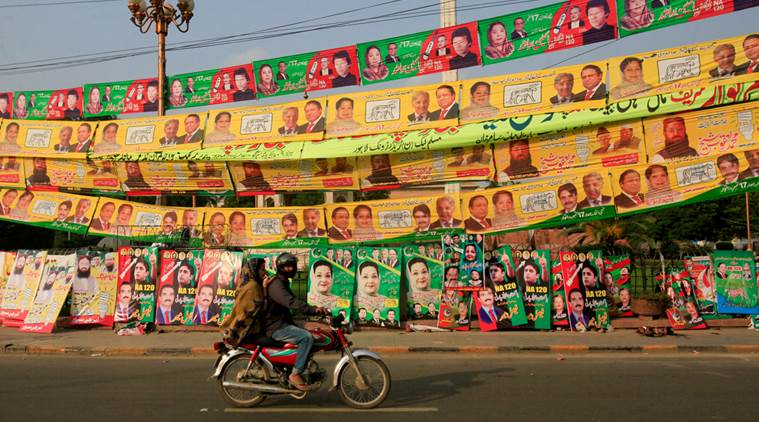 Residents ride on bike past election campaign signs along a road in Lahore, Pakistan. PHOTO: REUTERS