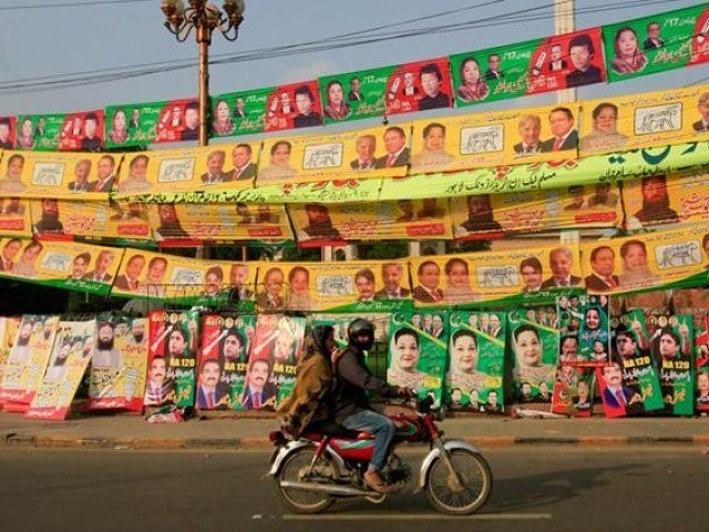 Residents ride on bike past election campaign signs along a road in Lahore. PHOTO: REUTERS