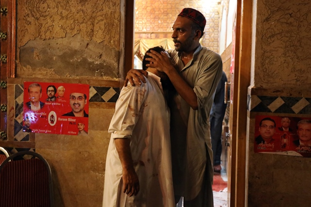 A party worker comforts another after the attack that killed at least 20 people. PHOTO: REUTERS