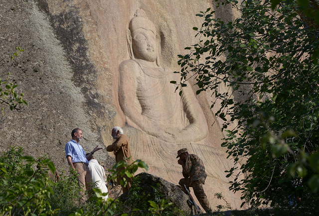 Experts speak next to the seventh-century rock sculpture of a seated Buddha carved into mountain in Jahanabad town in Swat. PHOTO: AFP.