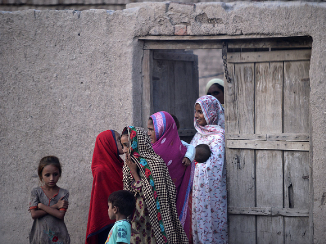 Pakistani villager women gather outside their home in Mohri Pur village, where women had previously been banned from voting.  PHOTO:AFP