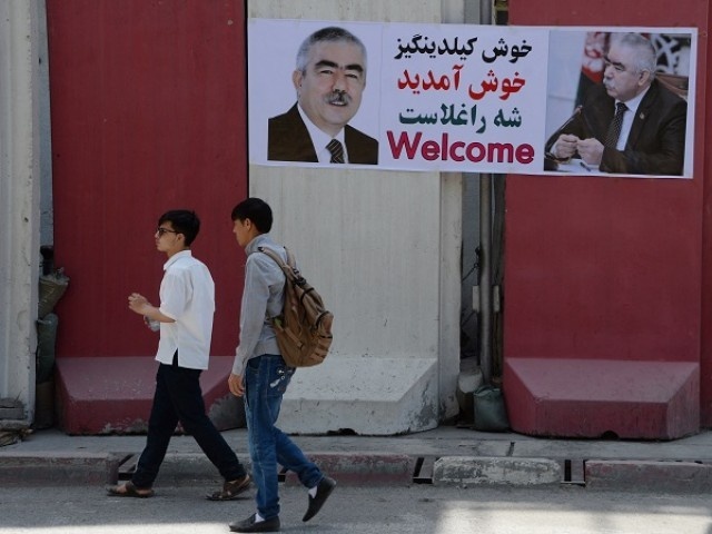 Afghan residents walk past a banner with the image of self-exiled Afghan Vice President Abdul Rashid Dostum ahead of his arrival to Kabul on July 22, 2018.  Dostum is expected to return to Kabul on July 22, more than a year after fleeing the country during an investigation into the rape and torture of a political rival. PHOTO: AFP