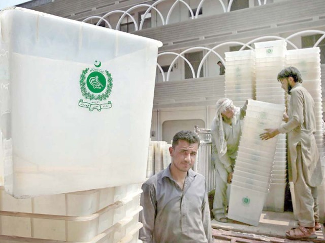Workers of ECP load ballot boxes in Peshawar on Monday. PHOTO: PPI