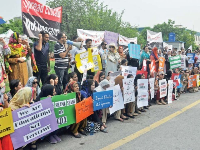 Members of All Pakistan Private Schools and Colleges Association hold protest against CDA sealing schools in Islamabad. PHOTO: ZAFAR ASLAM/EXPRESS