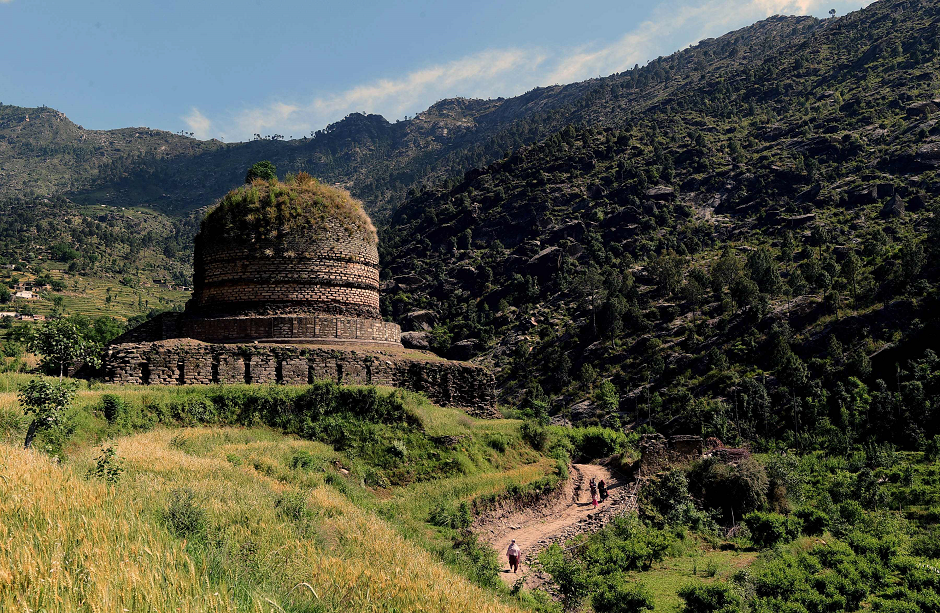 Pakistani visitors walking past a centuries-old stupa, a dome-shaped Buddhist monument, in the town of Amluk Dara near Mingora, the capital of the Swat Valley. PHOTO: AFP.