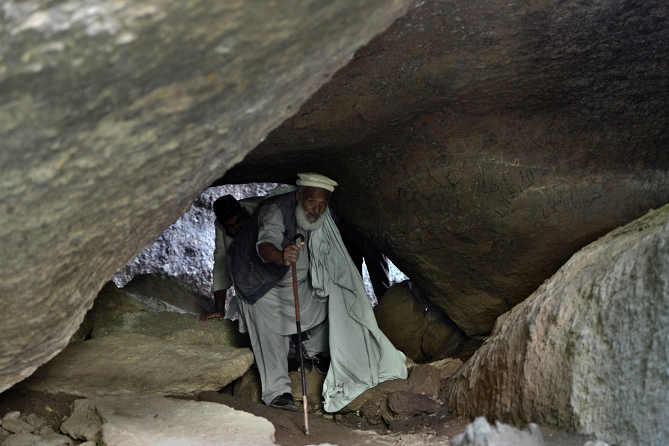 Pakistani historian Akhtar Munir walking with the help of a stick as he leads local tourists at the site of the seventh-century rock sculpture of a seated Buddha carved into a mountain in Jahanabad town in  Swat Valley. PHOTO: AFP.