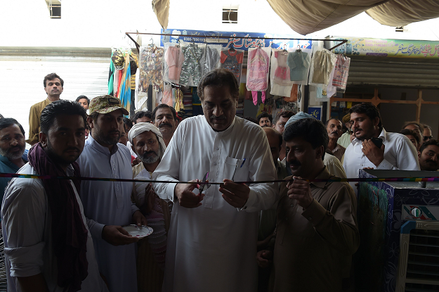 Raza Hayat Hiraj one of the favorite local candidates, cutts a ribbon during the inauguration ceremony of the election office at his constituency. PHOTO:AFP