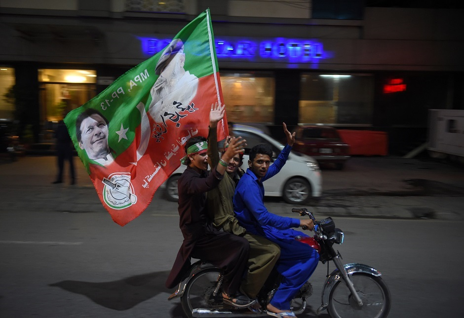 Supporters of Pakistan's cricketer-turned politician Imran Khan, head of the Pakistan Tehreek-e-Insaf (Movement for Justice) party, ride on a motorcycle as they celebrate in Rawalpindi on July 25, 2018, after voting closed in a general election. Vote-counting was ongoing on July 25 in a knife-edge Pakistan general election as former cricket hero Imran Khan sought power on a day marred by a bloody suicide bombing and claims of military interference. / PHOTO: AFP