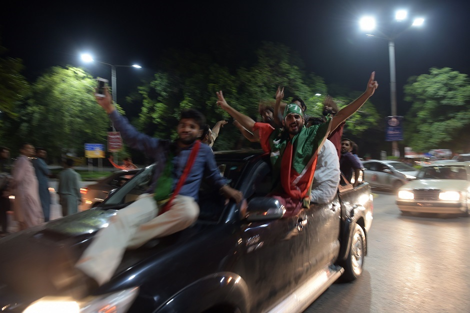 Supporters of Pakistan's cricketer-turned politician Imran Khan, head of the Pakistan Tehreek-e-Insaf (Movement for Justice) party, celebrate on a street during general election in Islamabad on July 25, 2018. Vote-counting was ongoing on July 25 in a knife-edge Pakistan general election as former cricket hero Imran Khan sought power on a day marred by a bloody suicide bombing and claims of military interference. PHOTO: AFP