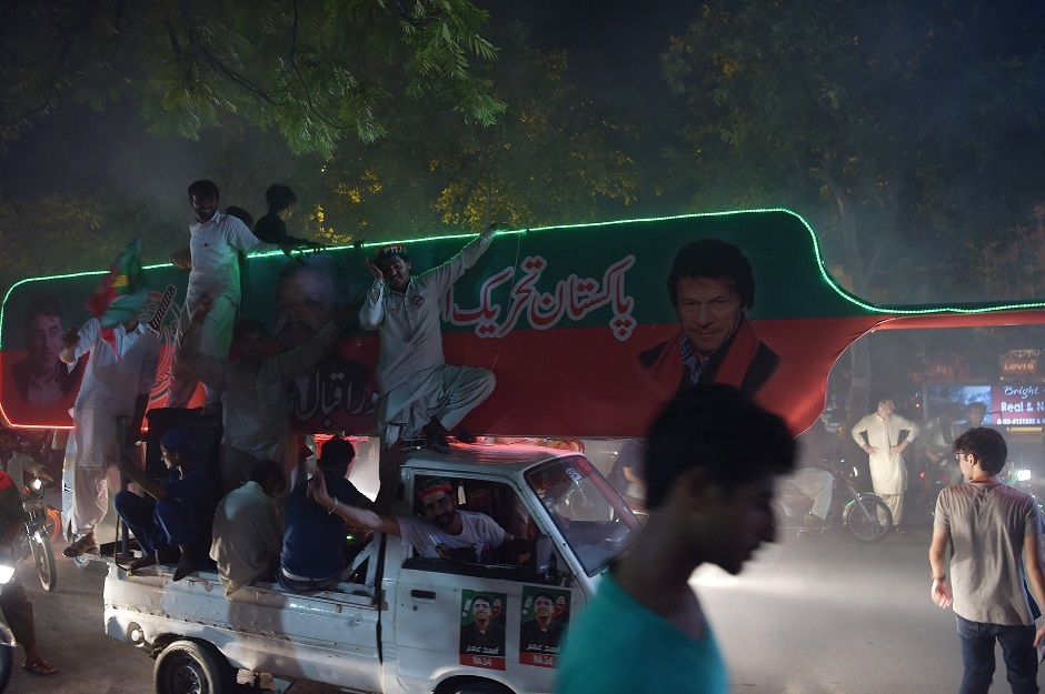 Supporters of Pakistan's cricketer-turned politician Imran Khan, head of the Pakistan Tehreek-e-Insaf (Movement for Justice) party, celebrate on a street during general election in Islamabad on July 25, 2018. Vote-counting was ongoing on July 25 in a knife-edge Pakistan general election as former cricket hero Imran Khan sought power on a day marred by a bloody suicide bombing and claims of military interference. PHOTO:AFP