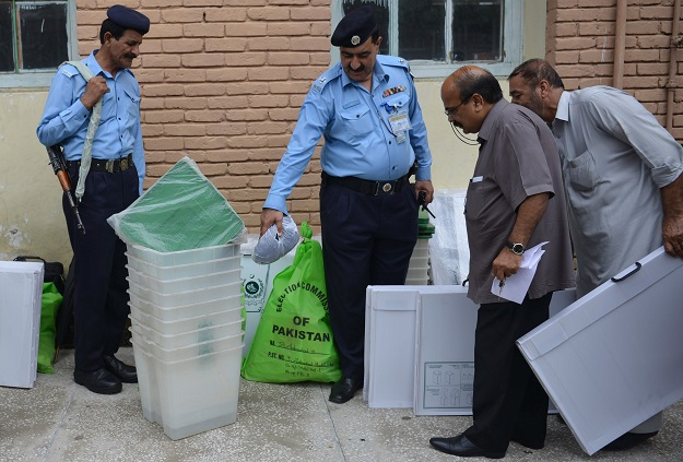 Pakistani police stand guard as election officials look at election materials at a distribution centre in Islamabad on July 24, 2018. Pakistan will hold its general election on July 25. PHOTO: AFP