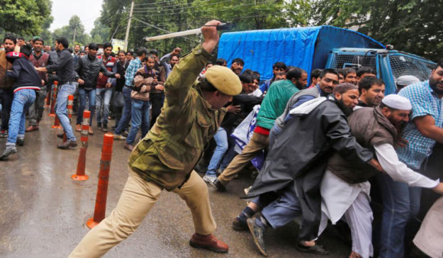 A police personnel canning protesters during a demonstration in Srinagar. PHOTO: REUTERS