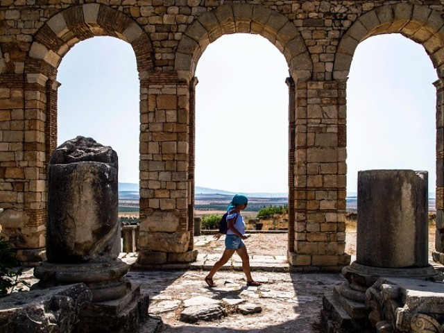 In this file photo taken on July 25, 2018, a tourist walks through the ruins of the ancient Roman site of Volubilis, near the town of Moulay Idriss Zerhounon in Morocco's north central Meknes region. Situated in the centre of a fertile plain at the foot of Mount Zerhoun, the towering remains of Morocco's oldest Roman site, Volubilis, were long neglected. But after decades of looting and decay, custodians of the now closely guarded ancient city are turning the page and attracting back tourists. PHOTO: AFP