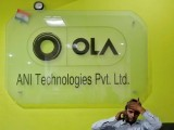 file-photo-an-employee-speaks-over-his-phone-as-he-sits-at-the-front-desk-inside-the-office-of-ola-cab-service-in-gurugram-2