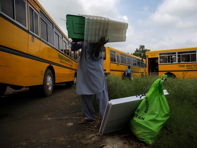 An election official carries election materials at a distribution centre ahead of general election in Islamabad, July 24 2018. PHOTO:REUTERS