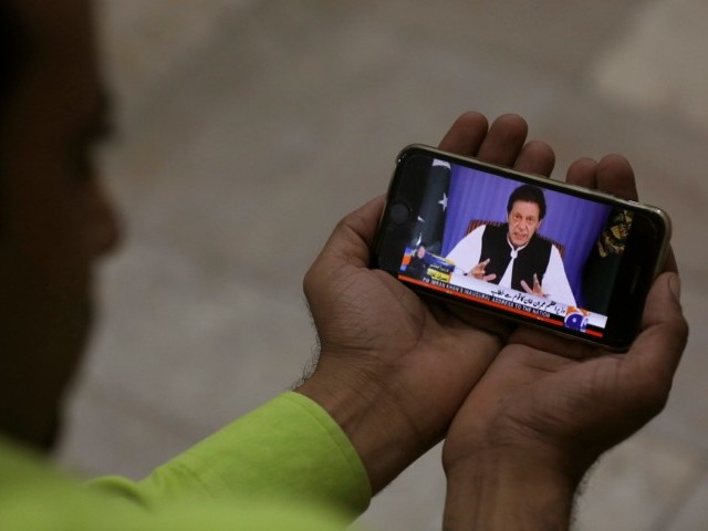 A man poses with a cell phone displaying PM Imran speaking to the nation in his first televised address. PHOTO: REUTERS
