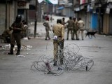 an-indian-policeman-pulls-concertina-wire-to-lay-a-barricade-on-a-road-during-a-curfew-in-srinagar-3