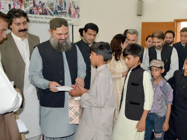 Balochistan Chief Minister Jam Kamal Khan distributes gifts among orphans at SOS Village on Eid. PHOTO: EXPRESS