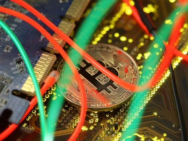 Representation of the Bitcoin virtual currency standing on the PC motherboard is seen in this illustration picture, February 3, 2018. PHOTO: REUTERS