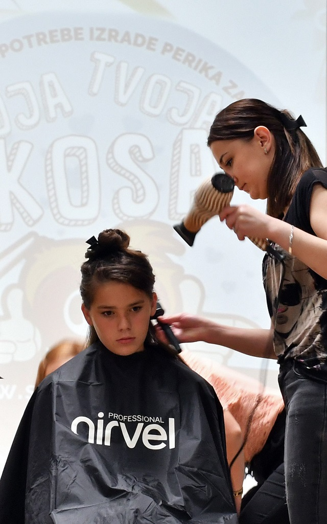 "A hairdresser prepares the hair of a young donor before snipping off some as part of the ""My Hair Your Hair"" campaign in Sarajevo on May 25, 2018. PHOTO: AFP"