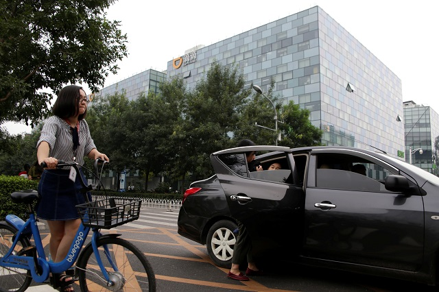 Passengers sit into a car provided by Didi Chuxing's Kuaiche service in front of its headquarters building in Beijing, China August 28, 2018. PHOTO: REUTERS