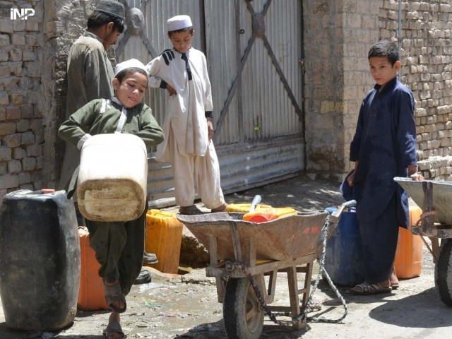 A boy uses his knee to lift a can filled with clean water in Quetta. PHOTO: INP