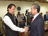 PM Imran greets the Chinese foreign minister.  PHOTO: EXPRESS