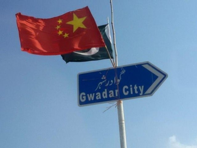 Chinese and Pakistani flags fly on a sign along a road towards Gwadar. PHOTO: REUTERS