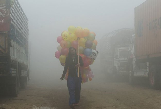 A Pakistani vendor carries balloons on a street amid heavy smog in Lahore. PHOTO: AFP