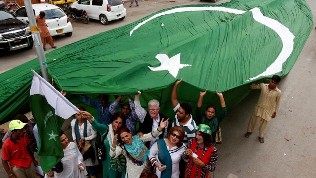 Supporters of civil rights group for transgender people, the Gender Interactive Alliance (GIA), dance and chant slogans as they pose with a national flag  in Karachi, August 2016. PHOTO:REUTERS