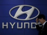 A car dealer stands in front of the logo of Hyundai Motor at its dealership in Seoul, South Korea, April 25, 2016. PHOTO: REUTERS