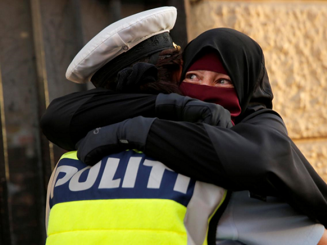A Danish policewoman embraces a niqab-clad protester. PHOTO: REUTERS