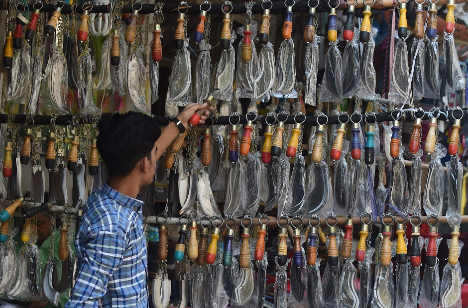 A man chooses knives mounted on chains during the first ten days of Muharram in Lahore on September 18, 2018. PHOTO:AFP