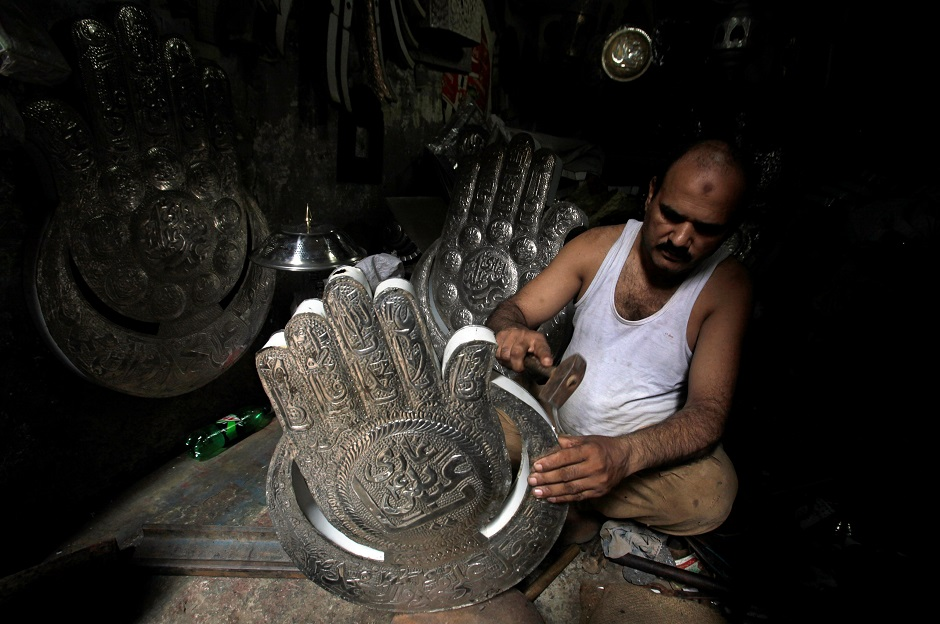 A man shapes a religious symbol for sale in preparation for the Ashura procession in Lahore on September 11, 2018. PHOTO:REUTERS
