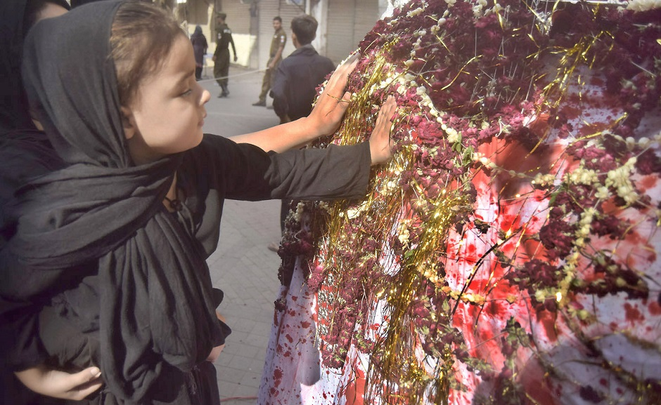 A girl touches the Zuljinnah in a Muharram procession in Lahore on September 19, 2018. PHOTO:NNI