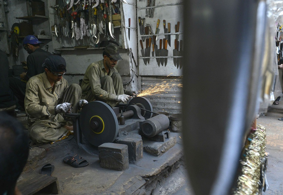 Pakistani vendors sharpen knives mounted on chains during the first ten days of Muharram in Lahore on September 18, 2018. PHOTO:AFP