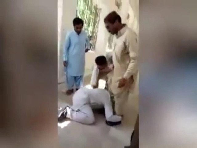 The girl's father who had come to the New Saeedabad Government Degree College for admission from the Senior College Clerk Janib Keerio is made to plead on his knees to him. SCREENGRAB: EXPRESS