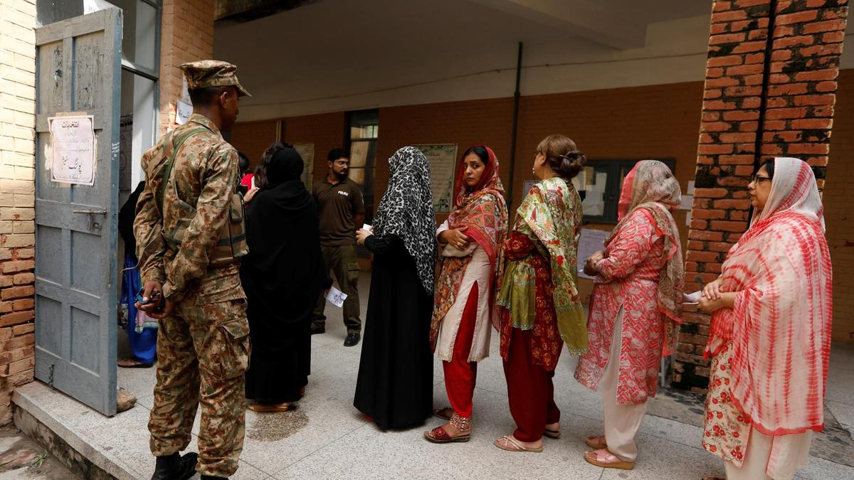 a-soldier-keeps-watch-as-voters-line-up-to-enter-at-a-polling-station-during-general-election-in-rawalpindi-2