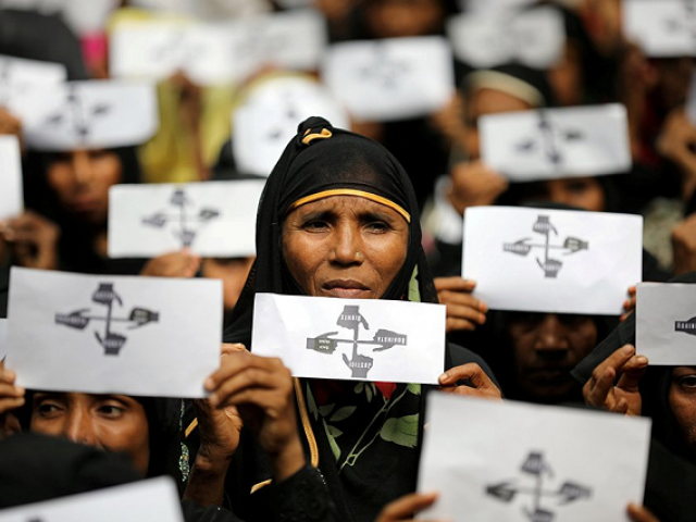 Rohingya refugee women hold placards as they take part in a protest at the Kutupalong refugee camp to mark the first anniversary of their exodus in Cox's Bazar, Bangladesh, August 25, 2018. PHOTO: REUTERS