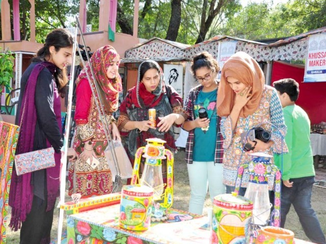 Women look at items on display, while schoolgirls enjoy a folk song at Lok Mela on Monday. PHOTOS: EXPRESS