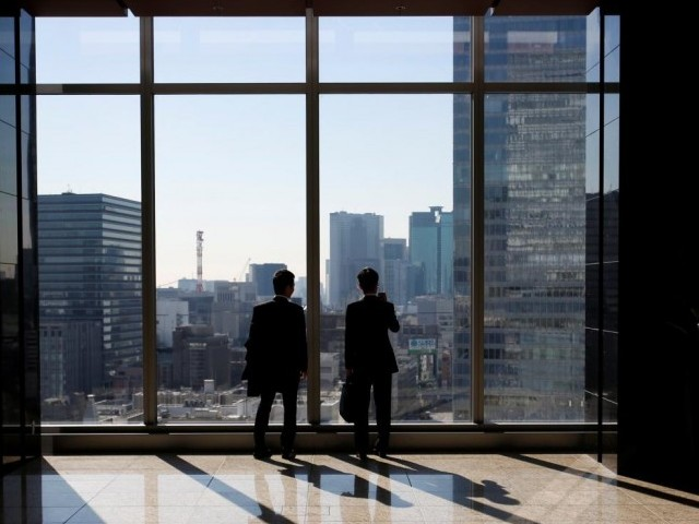 Businessmen are seen inside a high-rise office building. PHOTO: REUTERS