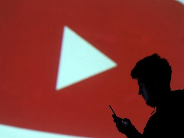 Silhouette of mobile user is seen next to a screen projection of Youtube logo in this