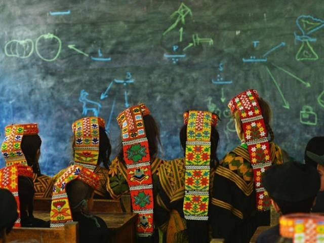 In this photograph taken on October 31, 2015, Kalash students attend a class at a school in the Brun village of Bumboret valley.  PHOTO: AFP