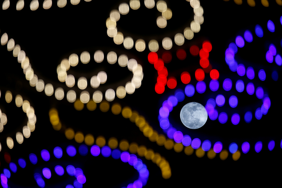 The rising full moon is seen behind Christmas lights in Valletta, Malta December 23, 2018. PHOTO: REUTERS
