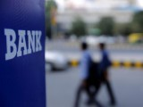 file-photo-commuters-walk-past-a-bank-sign-along-a-road-in-new-delhi-3-2-2