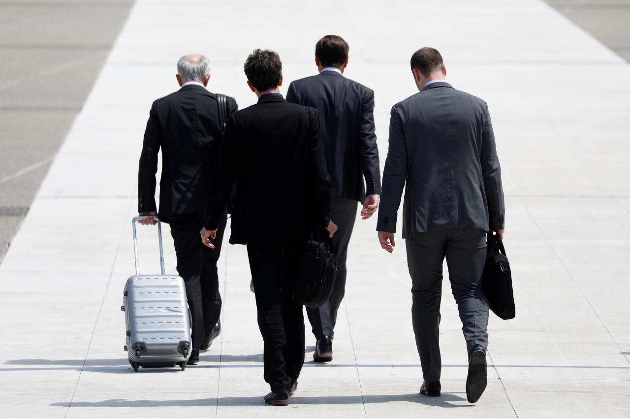 Representational image showing businessmen walk on a sideway. PHOTO: REUTERS