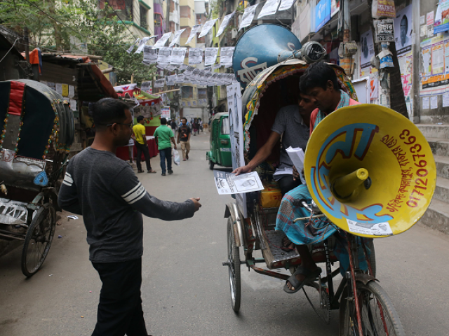 This photo taken on December 16, 2018 shows supporters of the ruling Bangladesh Awami League distributing leaflets to people during the general election campaign in Dhaka. PHOTO: AFP