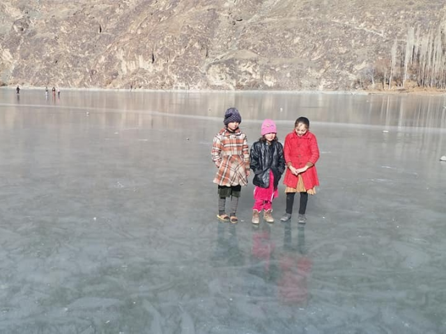 Children stand on a frozen lake near Gilgit Baltistan